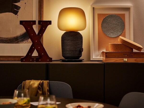 Candeeiro de mesa com coluna Wi-Fi SYMFONISK sobre uma prateleira, junto a várias peças de decoração e uma mesa com copos de vinho em primeiro plano.