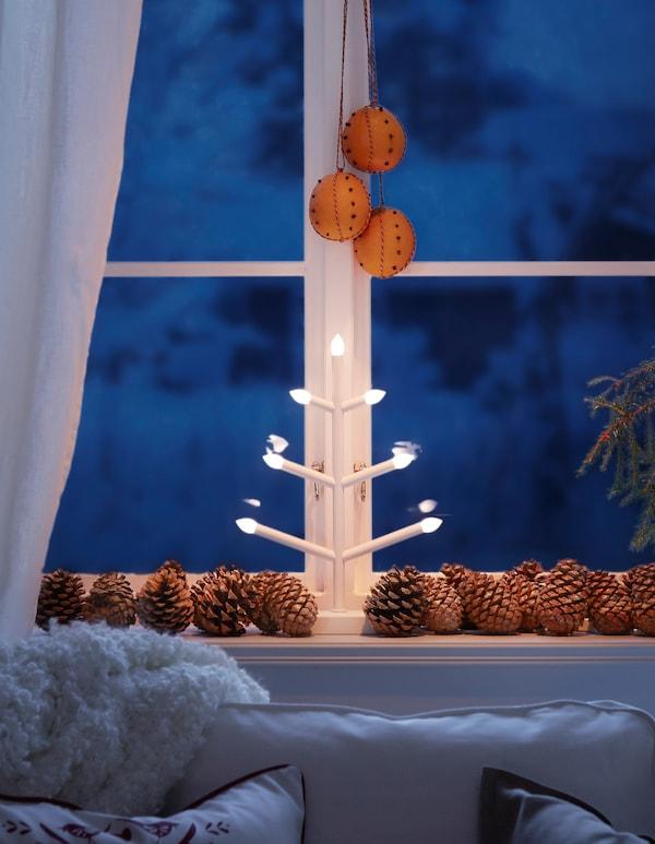 Candélabre blanc en forme d'arbre placé devant une fenêtre et entouré de pommes de pin, et oranges piquées de clous de girofle suspendues.