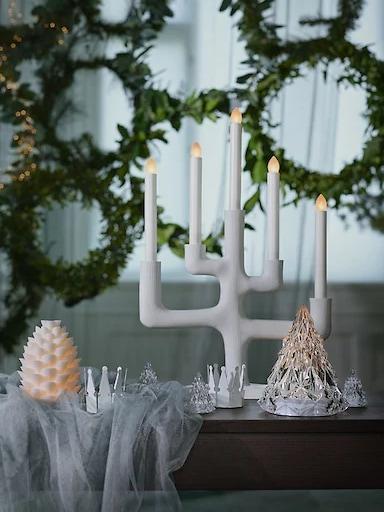Candelabro blanco STRÅLA de IKEA sobre una mesa frente a guirnaldas de Navidad.