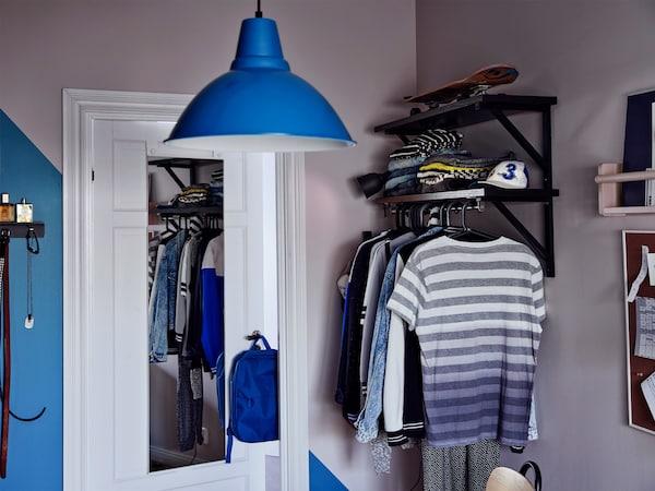 Cantó d'una habitació amb un mirall a la porta, un llum de sostre blau i roba penjada.