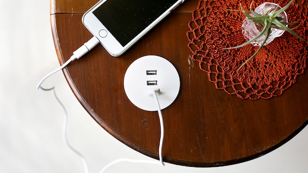 Caricabatteria USB NORDMÄRKE installato in un piano in legno rotondo. Un cellulare è collegato al caricabatteria con un cavo – IKEA