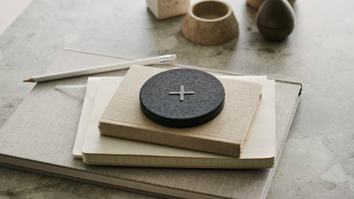 """Caricabatteria wireless NORDMÄRKE con grande simbolo """"+"""" sul rivestimento in tessuto grigio, in cima a una pila di libri su un tavolo."""