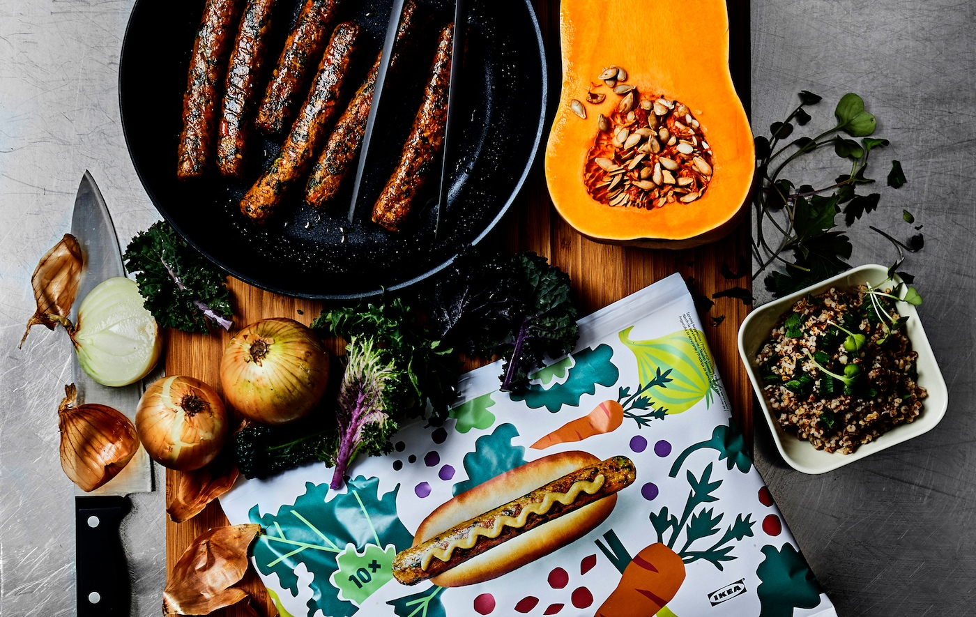 Cârnați într-o tigaie, legume și un ambalaj cu model pentru hotdog pe un tocător din lemn.