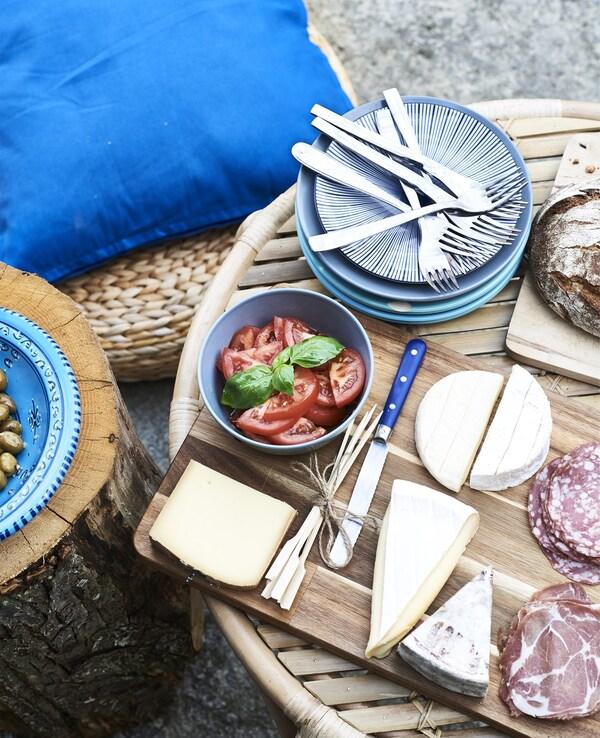 Carnes, queixos e vaixela azul nunha mesa de centro.