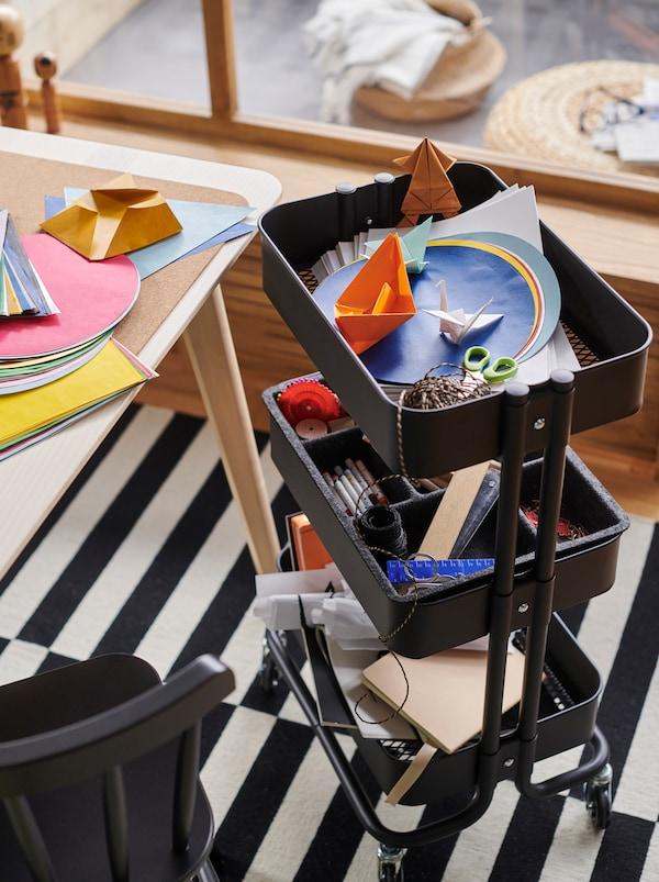 Carrello RÅSKOG nero con prodotti per le attività artistiche, vicino a un tavolo coperto di fogli di carta colorata.