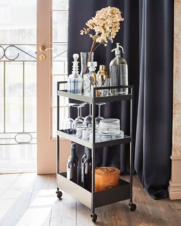 Carrinho NISSAFORS em preto com rodízios, com um sifão para refrigerante, vários copos, algumas garrafas e uma planta numa jarra de vidro.