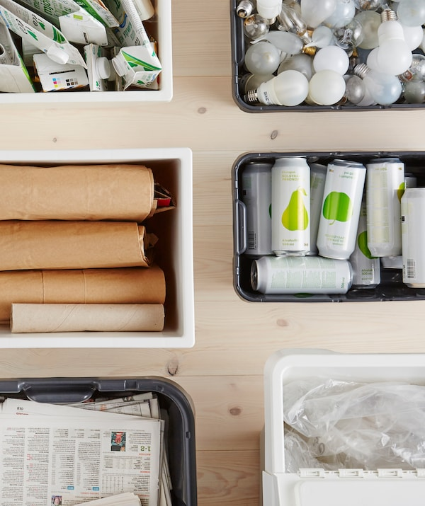 Cartons, cartons, journaux, ampoules, canettes et plastiques triés dans des boîtes de recyclage.