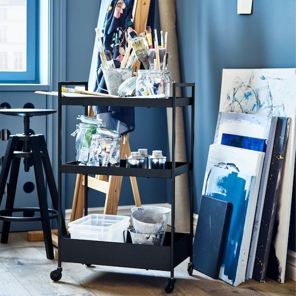 Căruciorul NISSAFORS negru, cutii de depozitare din plastic și un scaun de bar negru.