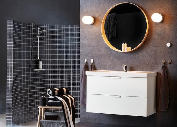 Casa de banho escura com um móvel de lavatório branco e um espelho dourado redondo.