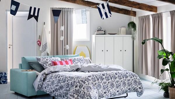 Casa de verán con fiestras cubertas por cortinas de opacas. Sofá cama VIMLE de dúas prazas con roupa de cama JUNIMAGNOLIA.