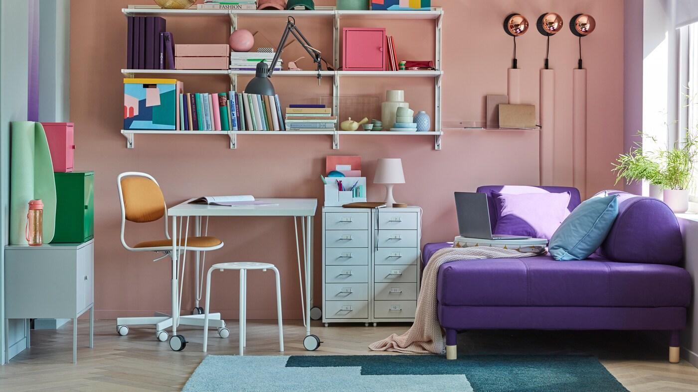 Casa pequeña con una mesa LINNMON/KRILLE blanca con patas sobre ruedas, varias estanterías, armarios y un sofá cama.