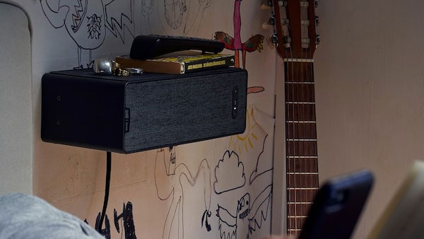 Cassa Wi-Fi da scaffale SYMFONISK, una chitarra appoggiata a fianco e graffiti sulla parete - IKEA