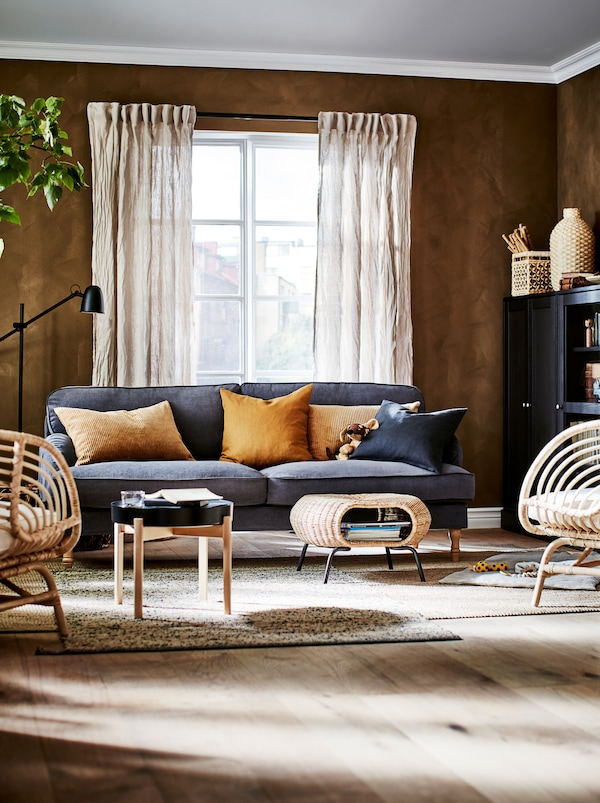 Časť obývacej izby v sýtych prírodných farbách s úložnými priestormi, sedením, príručným stolíkom a podnožkou GAMLEHULT.