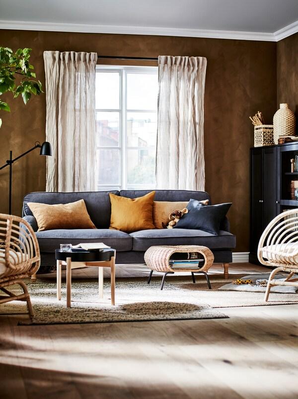 Část obývacího pokoje zařízeného sytými barvami a přírodními materiály - pohovkou, stolkem a podnožkou GAMLEHULT.