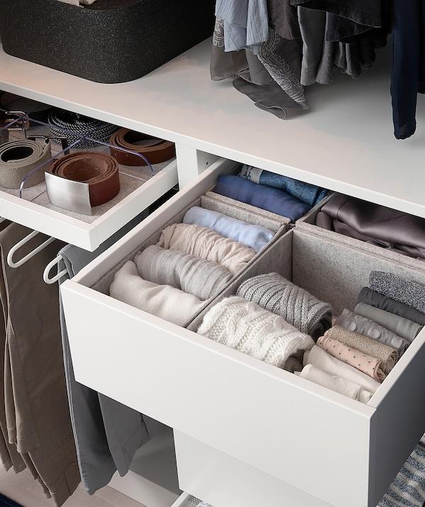 Část šatní skříně s uloženým oblečením, zavěšenými kalhotami a pásky v zásuvce
