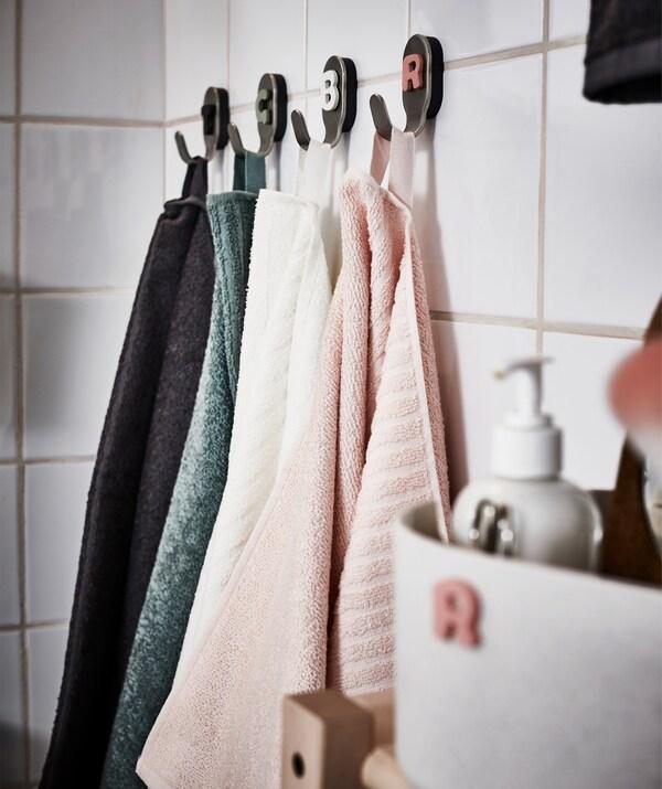 Catro toallas de diferentes cores que colgan de senllos ganchos de baño nun baño de azulexos brancos.