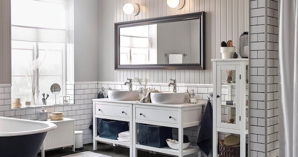 Two white sink vanity cabinets next to each other with a horizontally hung mirror in a tiled bathroom with a window.