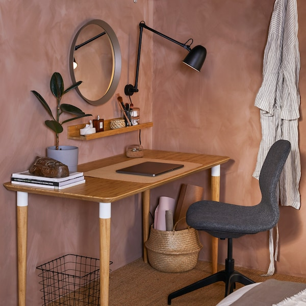 A desk in bamboo with white details, a black wall lamp, a round mirror and a dark grey conference chair.