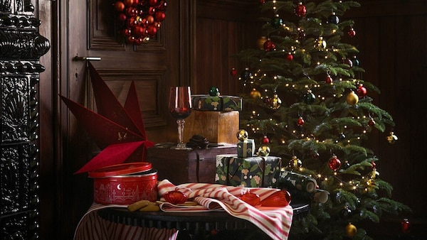 A table in front of a christmas tree with IKEA VINTER 2020 and VINTERSAGA products on display.