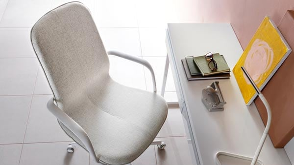 A beige LANGFJELL desk chair with white arms