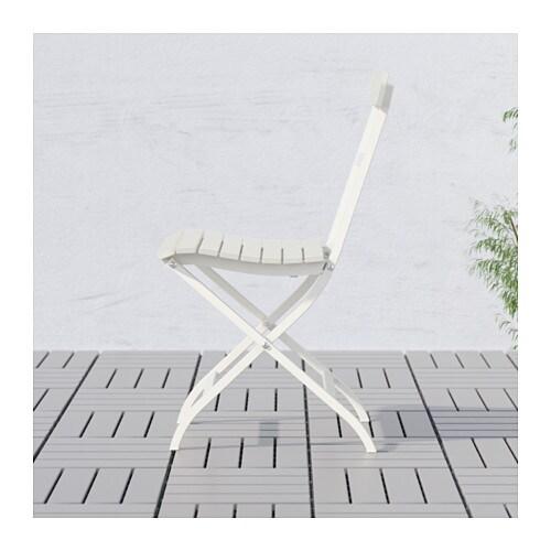 Man sitting outside on a MÄLARÖ stool beside another STACKHOLMEN stool.