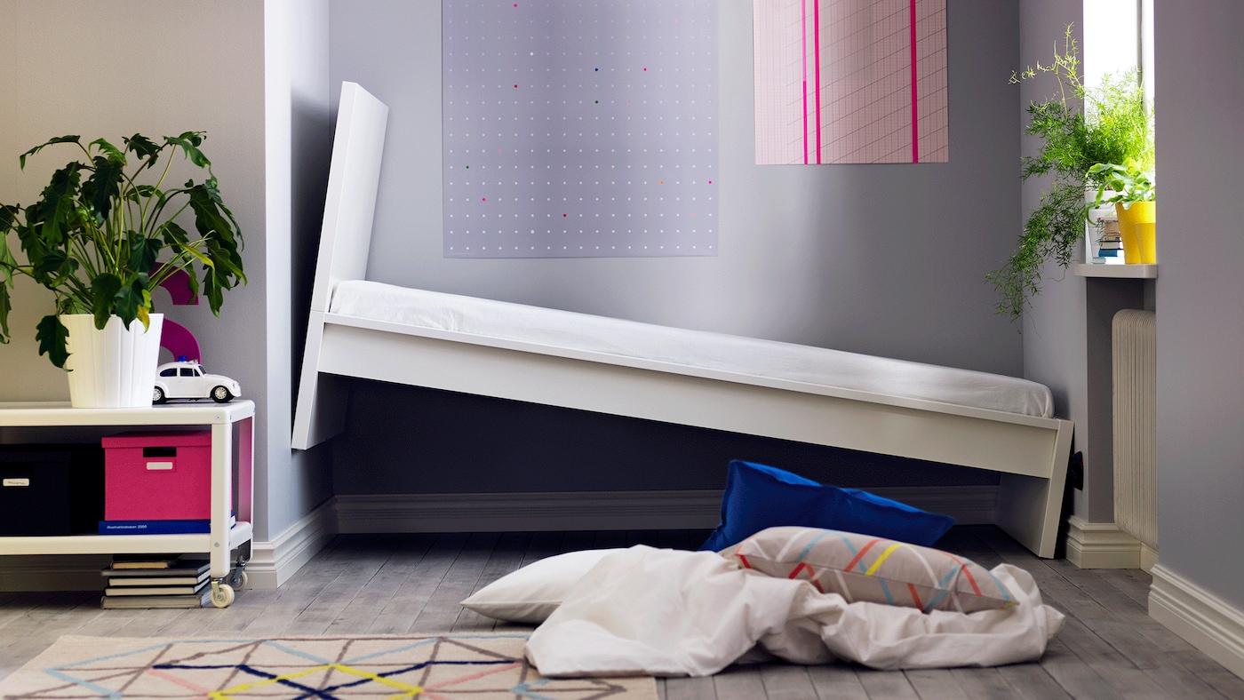 Cenário de um quarto, com duas camas demasiado grandes, que foram colocadas de forma desajeitada num ângulo em que um dos lados está no ar, não cabendo obviamente na divisão.