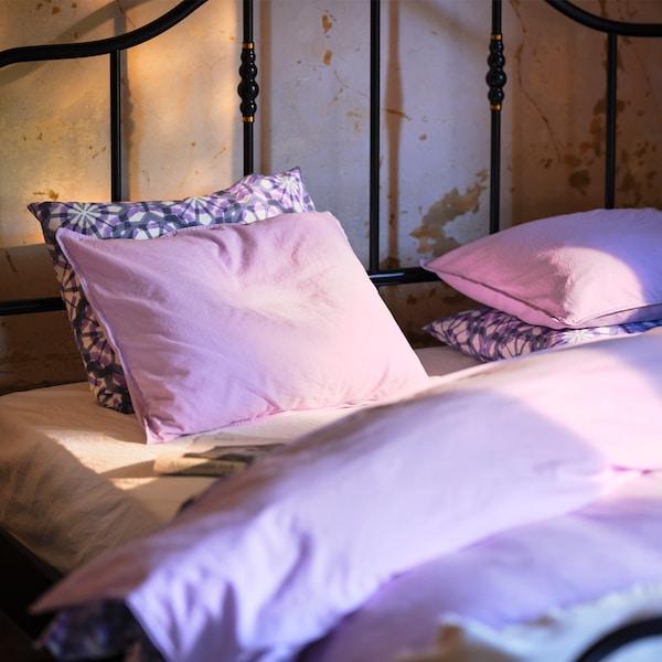 Černá postel s ocelovým rámem a světle fialovým povlečením