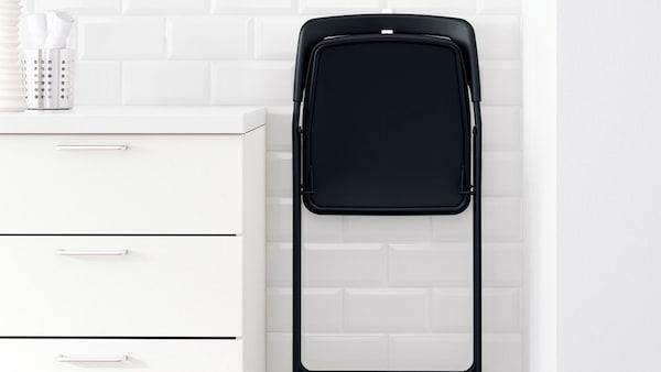 Černá skládací židle IKEA NISSE zavěšená na bílé zdi v úzkém prostoru mezi stěnou a skříní