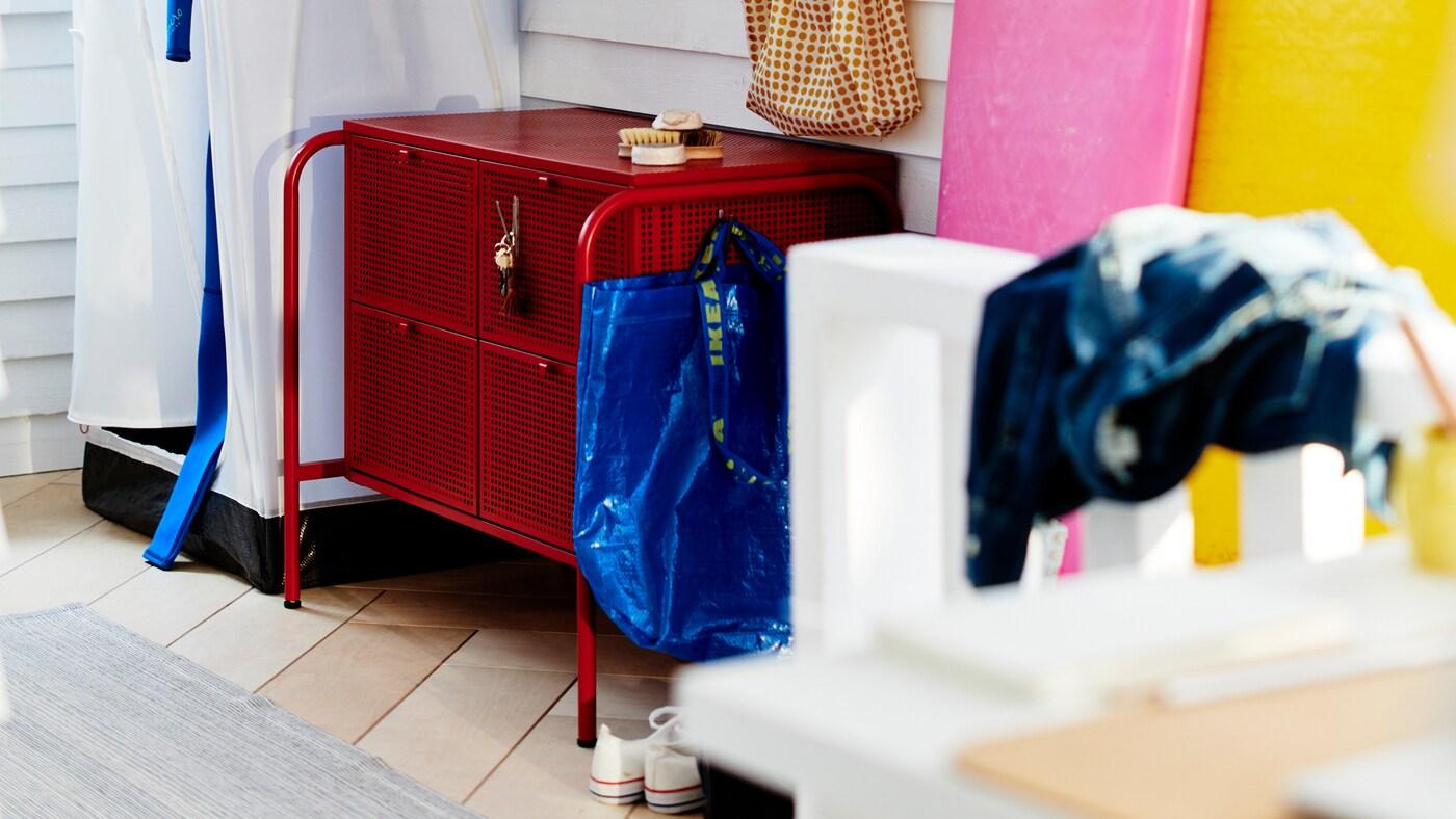 Červená komoda NIKKEBY s rôznymi doplnkami do predsiene v miestnosti s bielym dreveným obkladom.