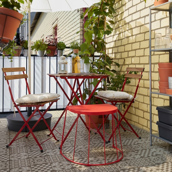 Červená stolička/príručný stolík TRANARÖ vedľa stola so stoličkami TÄRNÖ, ktoré ponúknu sedenie pre hostí.
