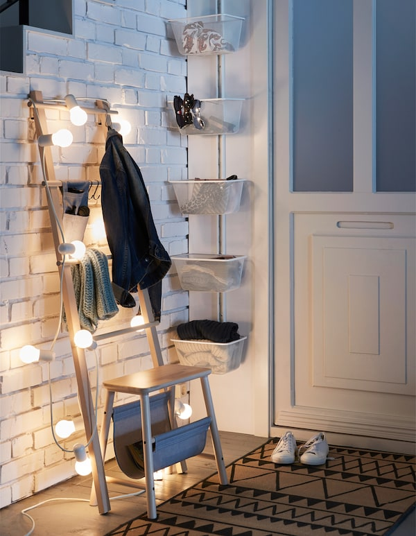 Cesta de almacenaje ALGOT en la puerta de entrada, junto con una escalera pequeña y un taburete, decorada con luces y utilizada como almacenaje en el pasillo.