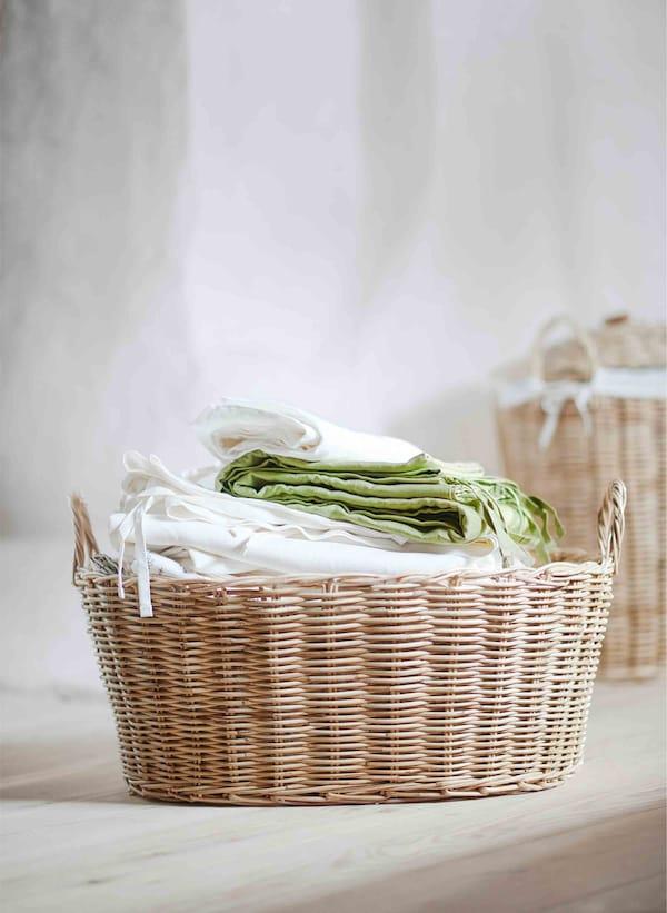 Cesta de ratán chea ata arriba de téxtiles de estilo natural.