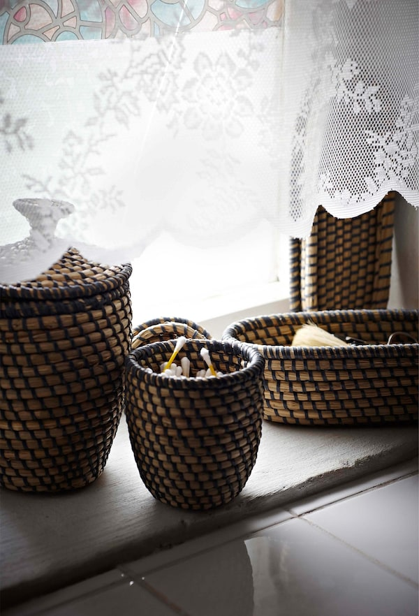 Cestas tejidas con fibras naturales en el alféizar de la ventana para almacenar pequeños objetos.