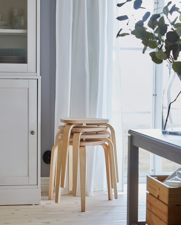 Četiri KYRRE stoličice od breze, složene pored prozora, pružaju dodatna sedišta za produženim trpezarijskim stolom.