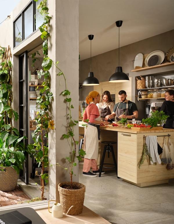 Četiri osobe oko velikog kuhinjskog otoka pripremaju hranu. Vrata su lagano otvorena i vode u dvorište s biljkama.