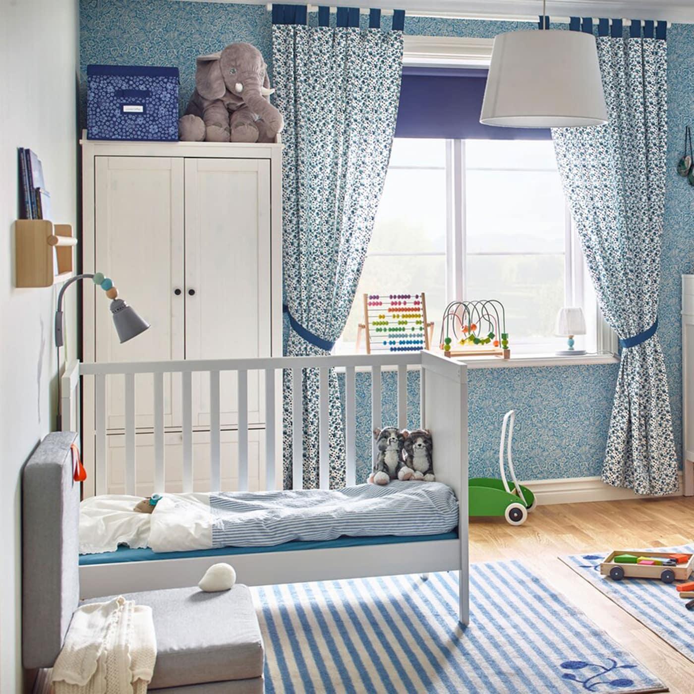 Cette paisible chambre bleue pour bébé, destinée à des jumeaux, comprend deux lits bébé IKEA SUNDVIK en blanc, de style traditionnel, et une table à langer SUNDVIK dotée de deux tiroirs et une tablette.