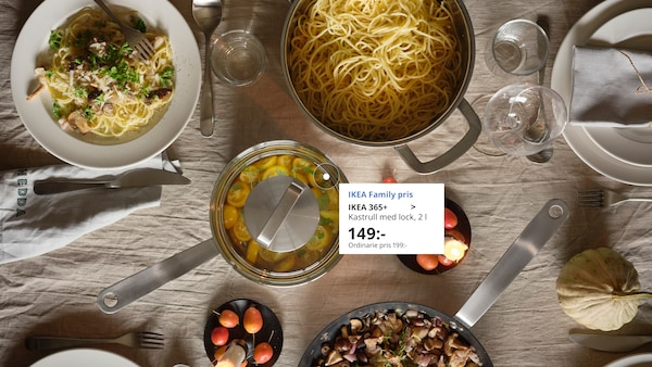 En bild ovanifrån på ett dukat bord med en kastrull utan lock med spagetti i och en kastrull med lock i klarglas. På dukningen som är gjord på en beige duk man ser även några tallrika i vitt porslin och glas.