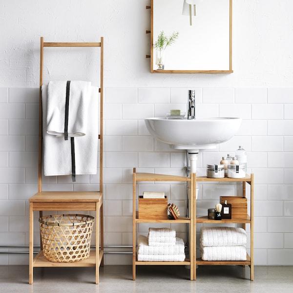 Chaise en bambou RÅGRUND avec porte-serviettes à côté de l'étagère d'évier en bambou RÅGRUND dans une salle de bain blanche.