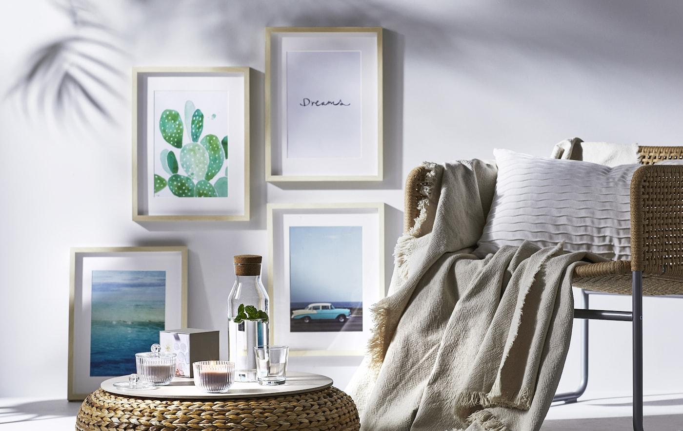 Chaise et repose-pieds en osier, avec cadres accrochés sur un mur blanc.