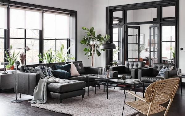 Chaise longuedun larruzko IKEA LANDSKRONA sofa beltz bat eta bi besaulki dituen eongela beltza, beixa eta zuria.