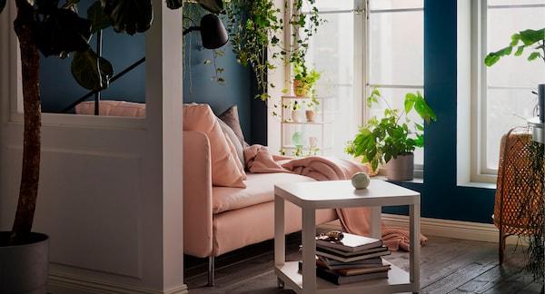 Chaiselongue junto a unas ventanas altas iluminadas por la luz del sol. Cojines, colcha y lámpara de lectura. Plantas en el alféizar, colgando y en los estantes de la pared.