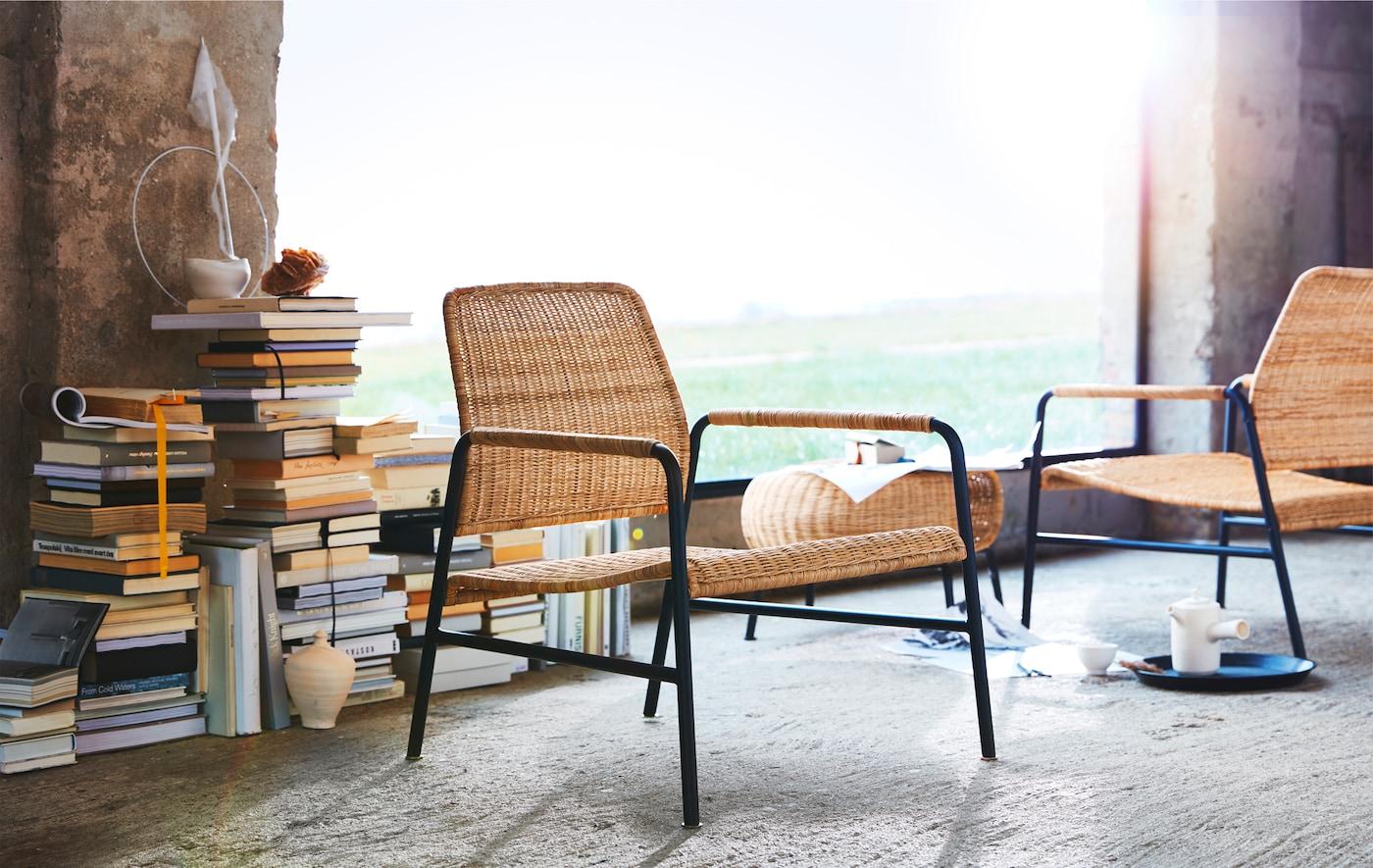 Chaises en rotin et en métal et repose-pieds devant une pile de livres et une grande fenêtre.