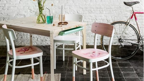 Chaises IDOLF blanches peintes en rose sur une table en bois