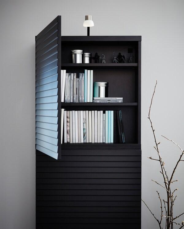 チャコールのアクセント扉のキャビネットと、その上に載ったニッケルメッキのLEDランプ。扉は開いており、中に本が入っています。