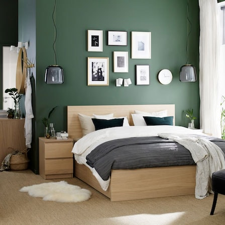 Chambre à coucher avec cadre de lit et table de chevet plaqués chêne blanchi, coiffeuse blanche et fauteuil gris.