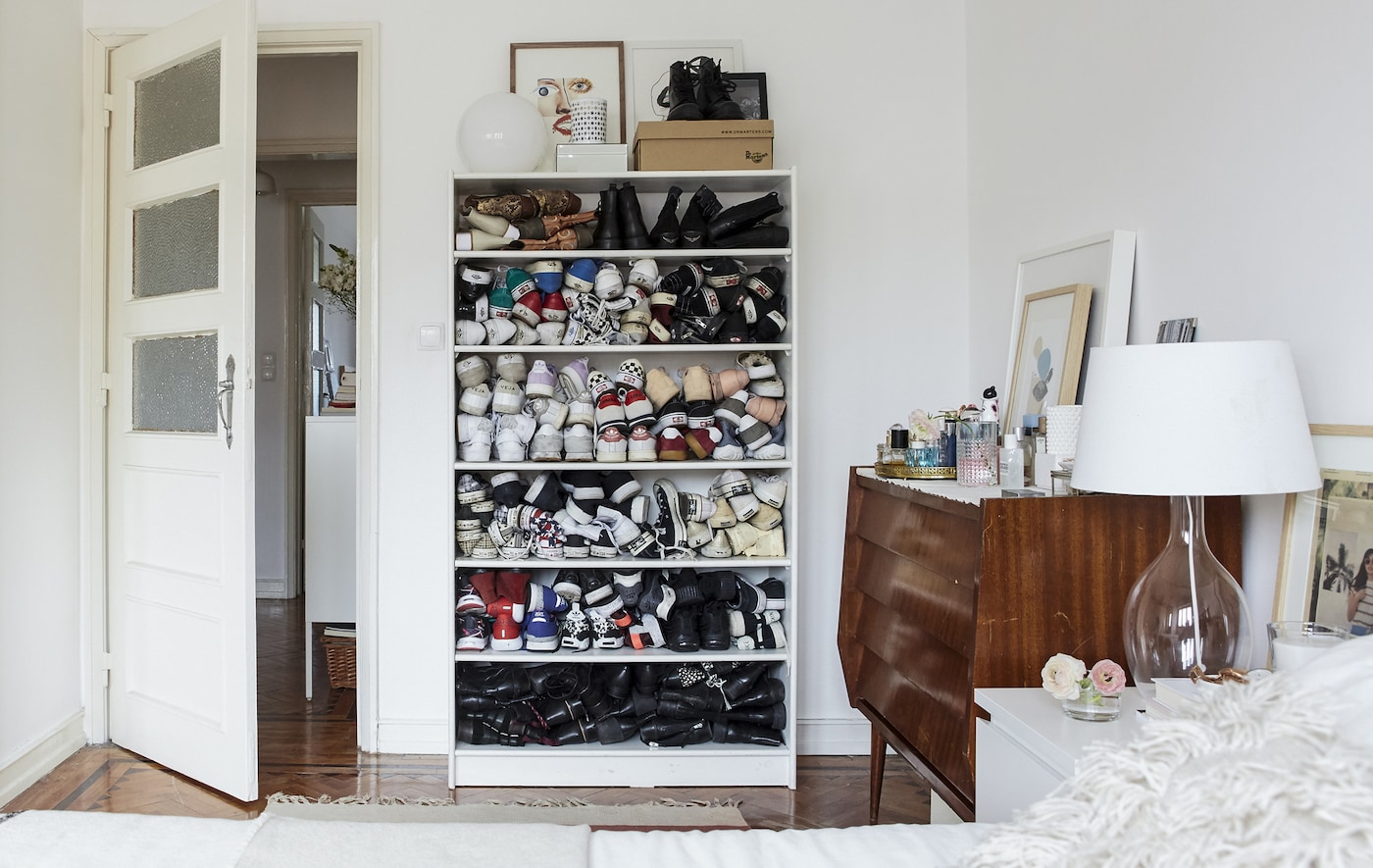 Chambre à coucher blanche avec parquet et chaussures empilées dans une bibliothèque.
