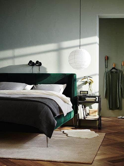 Chambre à coucher comprenant un lit TUFJORD vert avec des abat-jour REGOLIT au-dessus et des caissons à tiroirs NORDLI avec des livres près des fenêtres.