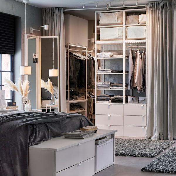 Chambre à coucher dans les tons de blanc et de gris, avec banquette à tiroirs blanche, garde-robe ouverte, rideaux gris clair et tapis en gris foncé.