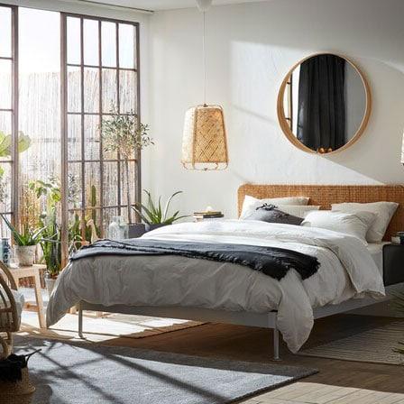 Chambre à coucher lumineuse où dominent les matières naturelles comme le rotin et le bambou. Près du lit, une grande baie vitrée donne accès à un espace extérieur.