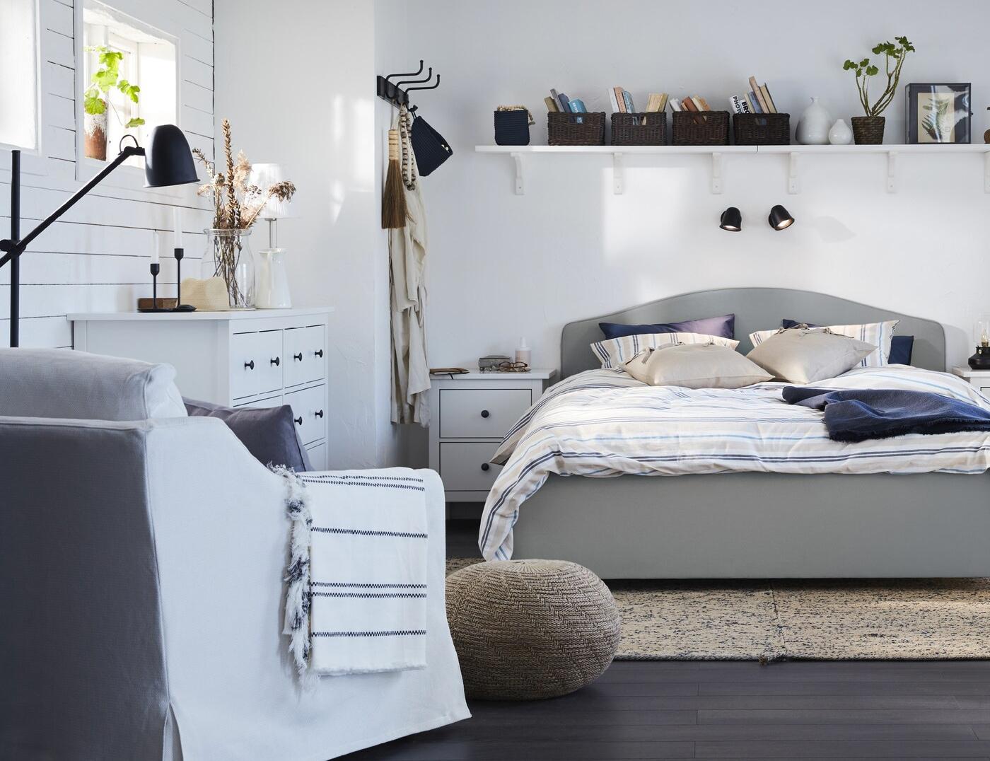 Chambre à coucher traditionnelle et agencée avec lit HAUGA beige, fauteuil blanc, rideaux blancs et bureau bleu-vert foncé.